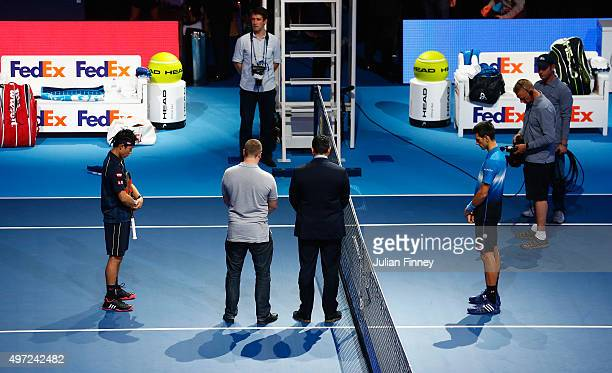 Novak Djokovic of Serbia and Kei Nishikori of Japan observe a minute's silence to remember those who lost their lives in the recent Paris attacks...