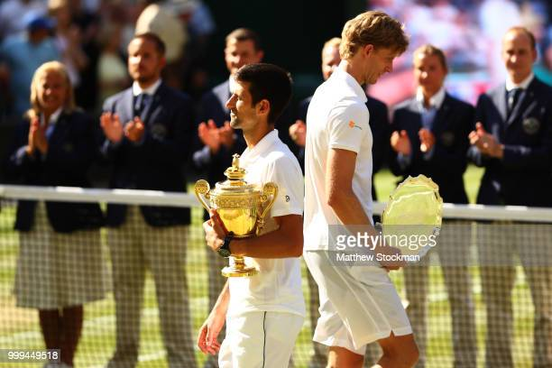 Novak Djokovic of Serbia and Kevin Anderson of South Africa hold their trophies after the Men's Singles final on day thirteen of the Wimbledon Lawn...