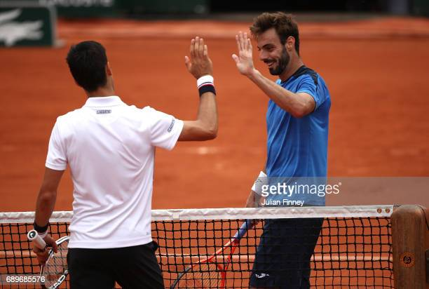 Novak Djokovic of Serbia and Marcel Granollers of Spain shake hands following their first round match on day two of the 2017 French Open at Roland...