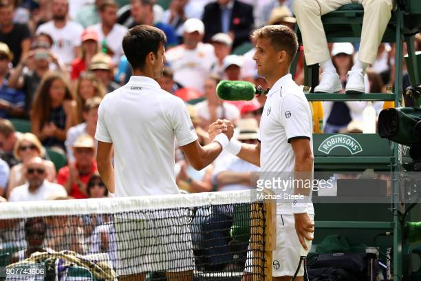 Novak Djokovic of Serbia and Martin Klizan of Slovakia shake hands after their during the Gentlemen's Singles first round match on day two of the...