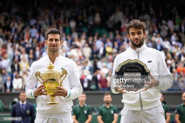 Novak Djokovic of Serbia and Matteo Berrettini of Italy stand together after receiving there trophies at The Wimbledon Lawn Tennis Championship at...