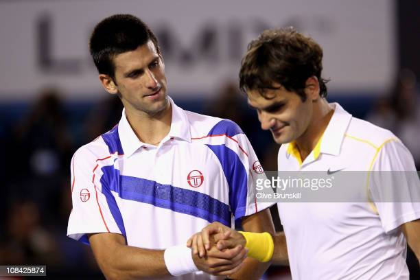 Novak Djokovic of Serbia and Roger Federer of Switzerland embrace at the net after their semifinal match during day eleven of the 2011 Australian...