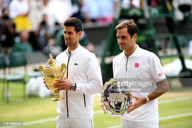 Novak Djokovic of Serbia and Roger Federer of Switzerland pose for a photo with their trophies after Men's Singles final against Roger Federer of...
