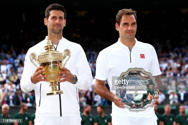 Novak Djokovic of Serbia and Roger Federer of Switzerland pose for a photo with their trophies after the Men's Singles final during Day thirteen of...