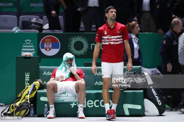 Novak Djokovic of Serbia and team mate Viktor Troicki react during Day Five of the 2019 Davis Cup at La Caja Magica on November 22 2019 in Madrid...
