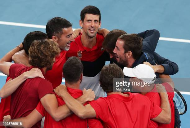 Novak Djokovic of Serbia and team mates celebrates winning the semifinal singles match against Daniil Medvedev of Russia during day nine of the 2020...