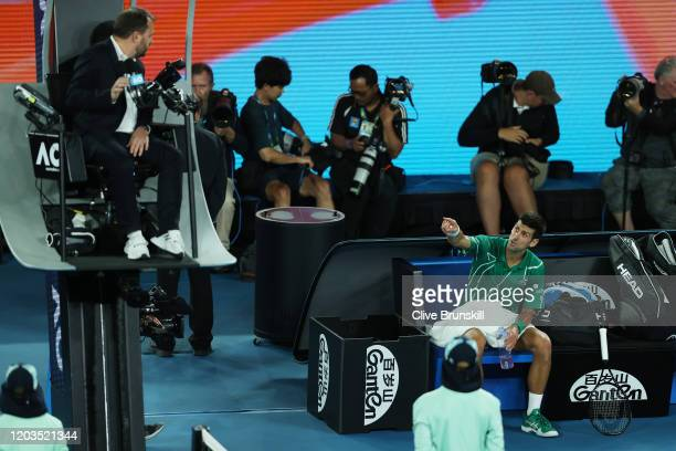 Novak Djokovic of Serbia argues with the chair umpire Damien Dumusois as he sits down in between games after being broken on serve in the second set...
