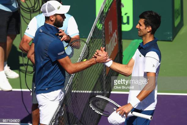 Novak Djokovic of Serbia at the net after his straight sets defeat by Benoit Paire of France in their second round match during the Miami Open...