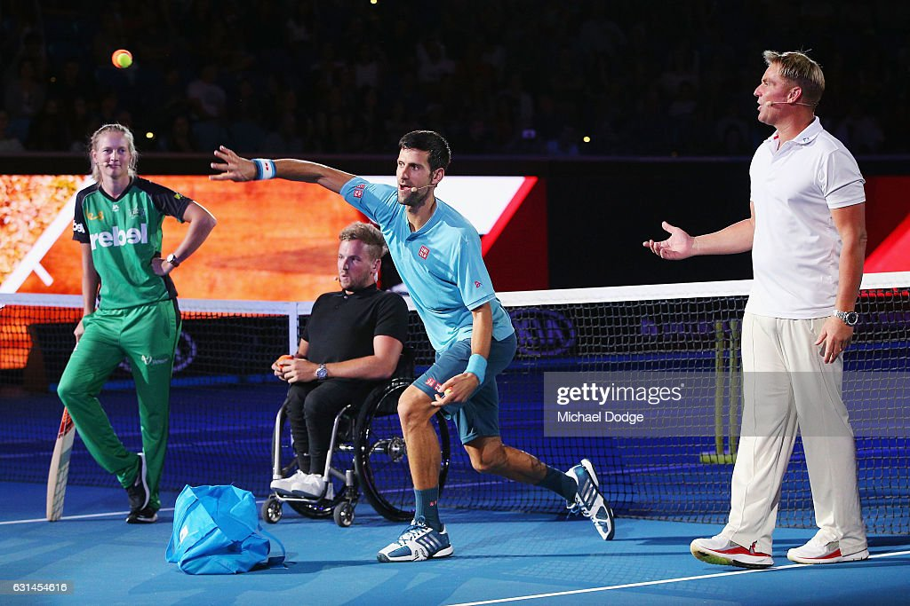 Novak Djokovic of Serbia bowls a tennis ball in front of Australian cricket legend Shane Warne during 'A Night with Novak' at Margaret Court Arena on January 11, 2017 in Melbourne, Australia.