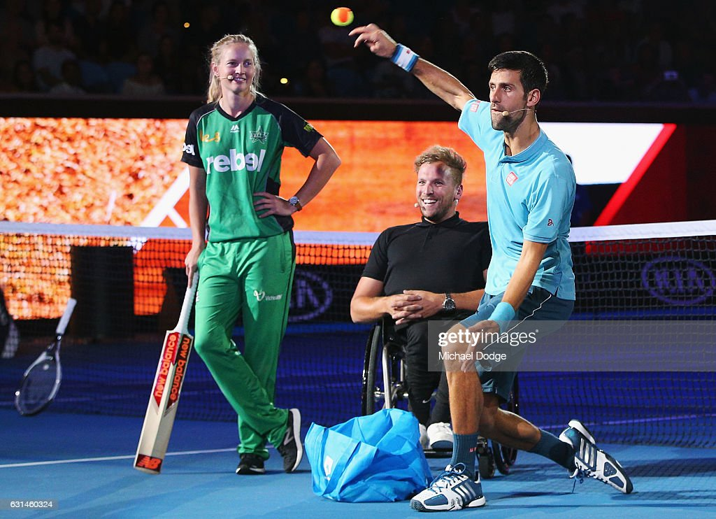 Novak Djokovic of Serbia bowls a tennis ball in front of Meg Lanning of the Melbourne Stars and wheelchair tennis player Dylan Alcott during 'A Night with Novak' at Margaret Court Arena on January 11, 2017 in Melbourne, Australia.