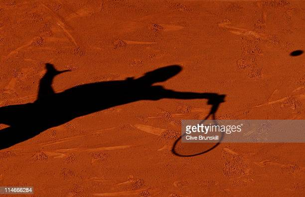 Novak Djokovic of Serbia casts a shadow on the clay as he hits a forehand during the men's singles round two match between Victor Hanescu of Romania...