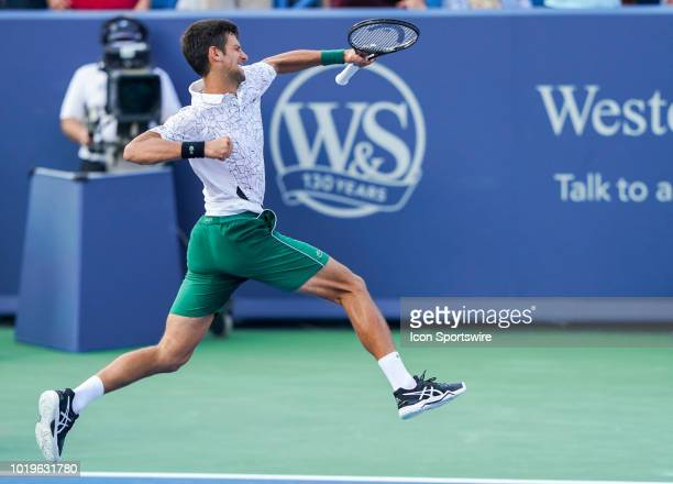 Novak Djokovic of Serbia celebrates and gets airborne after defeating Roger Federer of Switzerland in the Western Southern Open singles final at the...