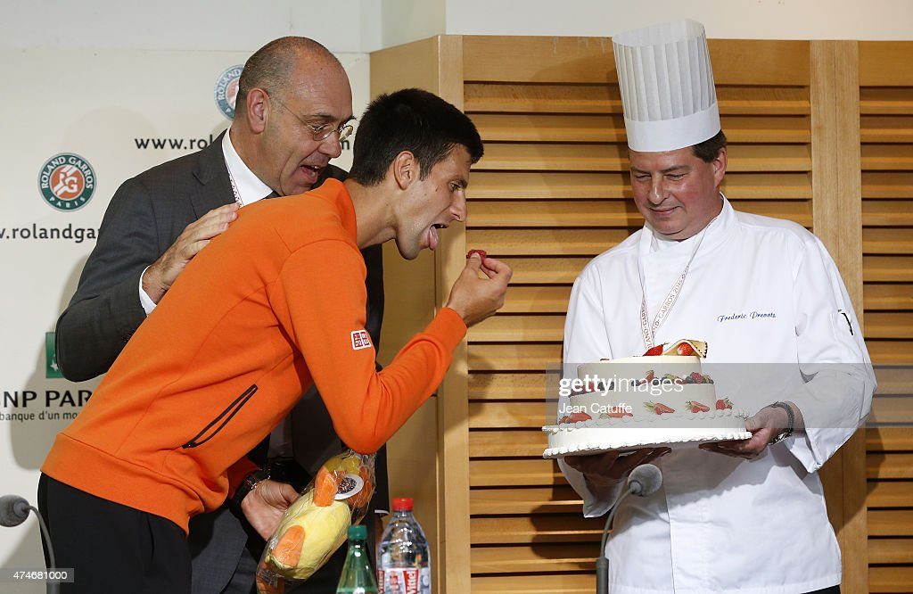 Novak Djokovic of Serbia celebrates his 28th birthday by eating a cake (without gluten) offered by the tournament and its director Gilbert Ysern (left) prior to the French Open 2015 at Roland Garros stadium on May 22, 2015 in Paris, France.