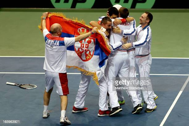 Novak Djokovic of Serbia celebrates his win in the fourth rubber against Sam Querrey with his teammates during the Davis Cup tie between the United...