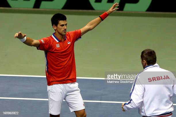 Novak Djokovic of Serbia celebrates his win in the fourth rubber against Sam Querrey with team captain Team Captain Bogdan Obradovic of Serbia during...