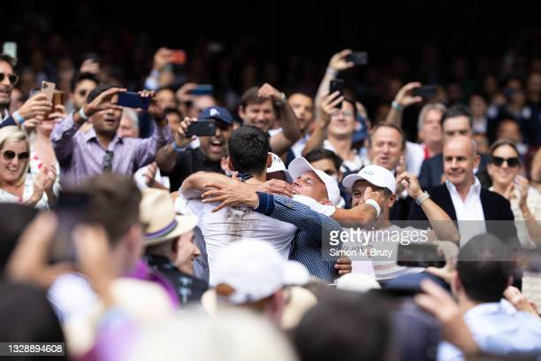 Novak Djokovic of Serbia celebrates victory with his coaches and agents during the Men's Singles Final against Matteo Berrettini of Italy at The...