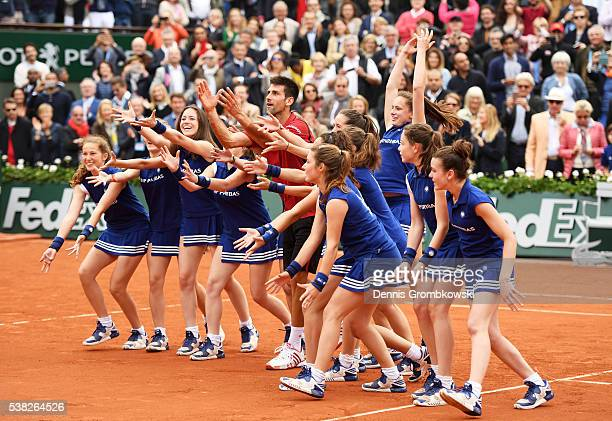 Novak Djokovic of Serbia celebrates victory with the help of the ball girls during the Men's Singles final match against Andy Murray of Great Britain...