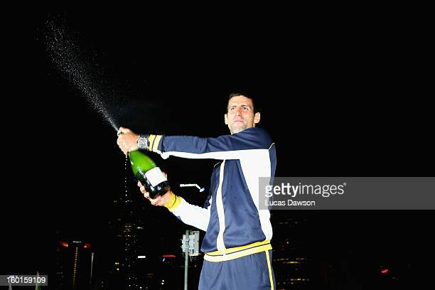 Novak Djokovic of Serbia celebrates with a bottle of champagne in the early hours of January 28 2013 after winning his men's final match against Andy...