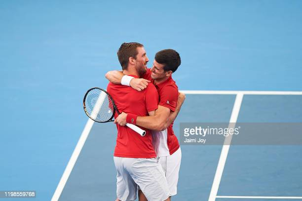 Novak Djokovic of Serbia celebrates with Serbian teammate Viktor Troicki after winning his quarter final singles match against Denis Shapovalov of...