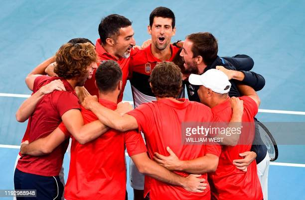 Novak Djokovic of Serbia celebrates with teammates after winning his men's singles match against Daniil Medvedev of Russia at the ATP Cup tennis...