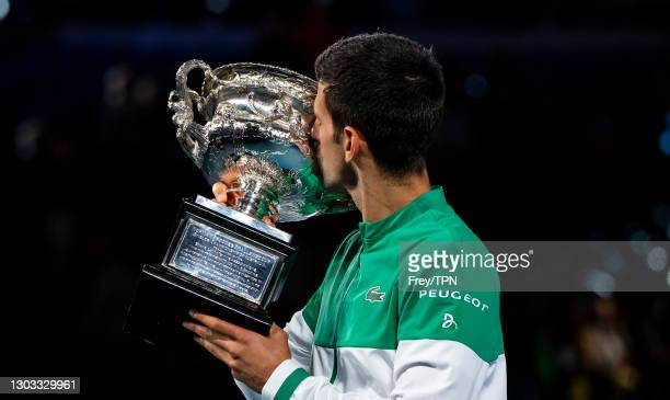 Novak Djokovic of Serbia celebrates with the trophy after beating Daniil Medvedev of Russia in the men's singles final during day 14 of the 2021...