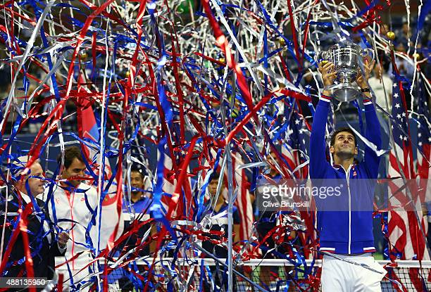 Novak Djokovic of Serbia celebrates with the trophy after defeating Roger Federer of Switzerland during their Men's Singles Final match on Day...