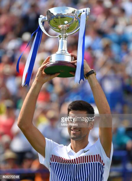 Novak Djokovic of Serbia celebrates with the trophy after victory in the mens singles final against Gael Monfils of France on day seven of the Aegon...