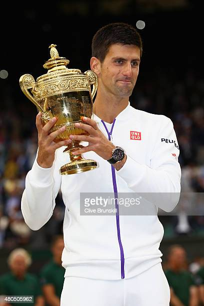 Novak Djokovic of Serbia celebrates with the trophy after winning the Final Of The Gentlemen's Singles against Roger Federer of Switzerland on day...