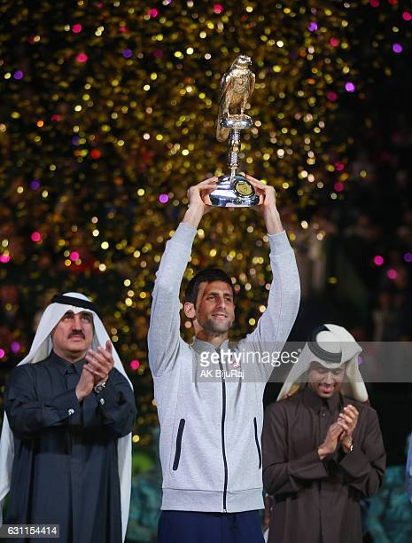 Novak Djokovic of Serbia celebrates with the trophy after winning the men's singles Final Of ATP Qatar Open tennis competition against Andy Murray of...