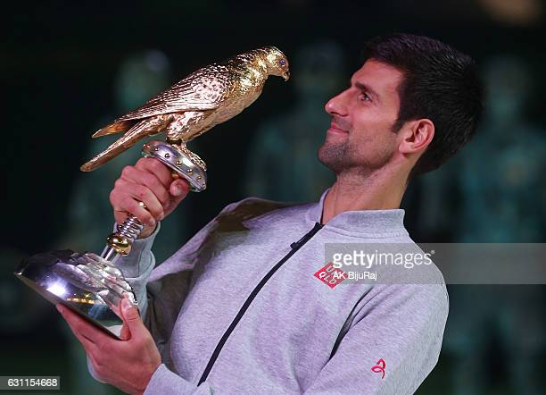 Novak Djokovic of Serbia celebrates with the trophy after winning the men's singles final of the ATP Qatar Open tennis competition against Andy...