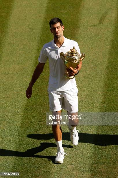 Novak Djokovic of Serbia celebrates with the trophy after winning the Men's Singles final against Kevin Anderson of South Africa on day thirteen of...
