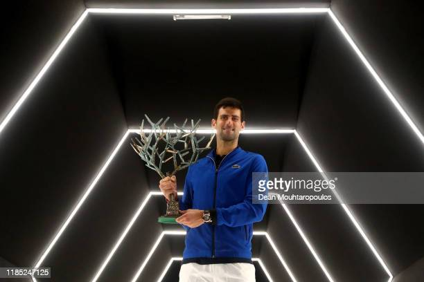 Novak Djokovic of Serbia celebrates with the trophy in the player walk in tunnel after victory in the Men's Singles Final match against Denis...