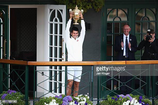 Novak Djokovic of Serbia celebrates with the trophy on the clubhouse balcony after winning the Gentlemen's Singles Final against Roger Federer of...