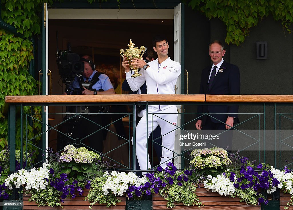 Novak Djokovic of Serbia celebrates with the trophy on the clubhouse balcony after winning the Final Of The Gentlemen's Singles against Roger Federer of Switzerland on day thirteen of the Wimbledon Lawn Tennis Championships at the All England Lawn Tennis and Croquet Club on July 12, 2015 in London, England.