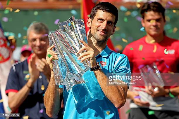 Novak Djokovic of Serbia celebrates with the winner's trophy after defeating Milos Raonic of Canada during the mens final of the BNP Paribas Open at...