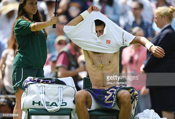 Novak Djokovic of Serbia changes his shirt during the Men's Singles first round against James Ward of Great Britain on day one of the Wimbledon Lawn...