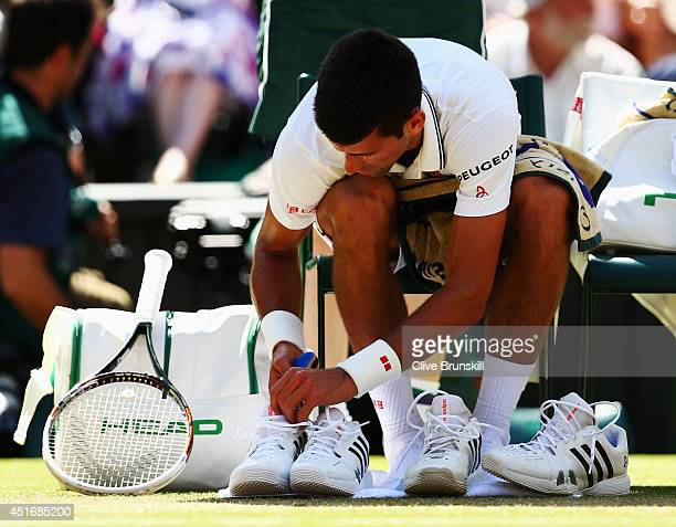 Novak Djokovic of Serbia changes his trainers during his Gentlemen's Singles semifinal match against Grigor Dimitrov of Bulgaria on day eleven of the...