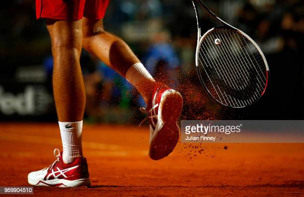 Novak Djokovic of Serbia clears clay from his shoes in his match against Kei Nishikori of Japan in the Quarter Finals during day six of the...