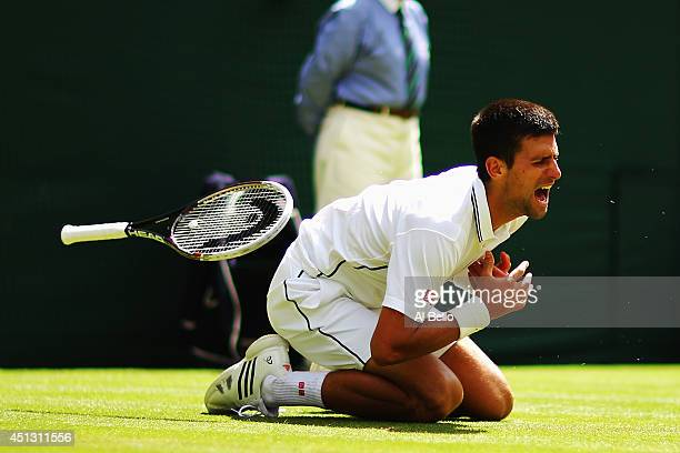 Novak Djokovic of Serbia clutches his injured shoulder after he falls over making a return during his Gentlemen's Singles third round match against...