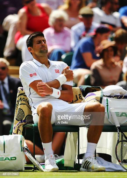Novak Djokovic of Serbia clutches his shoulder which he injured after a fall during his Gentlemen's Singles third round match against Gilles Simon of...