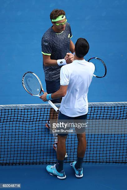 Novak Djokovic of Serbia congratulates Denis Istomin of Uzbekistan after winning their second round match on day four of the 2017 Australian Open at...