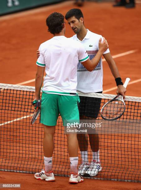 Novak Djokovic of Serbia congratulates his opponant Dominic Thiem of Austria on victory following the mens singles quarter finals match on day eleven...