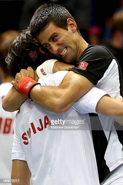 Novak Djokovic of Serbia congratulates Ilija Bozoljac of Serbia after his win with Nenad Zimonjic of Serbia over Mike and Bob Bryan in the third...