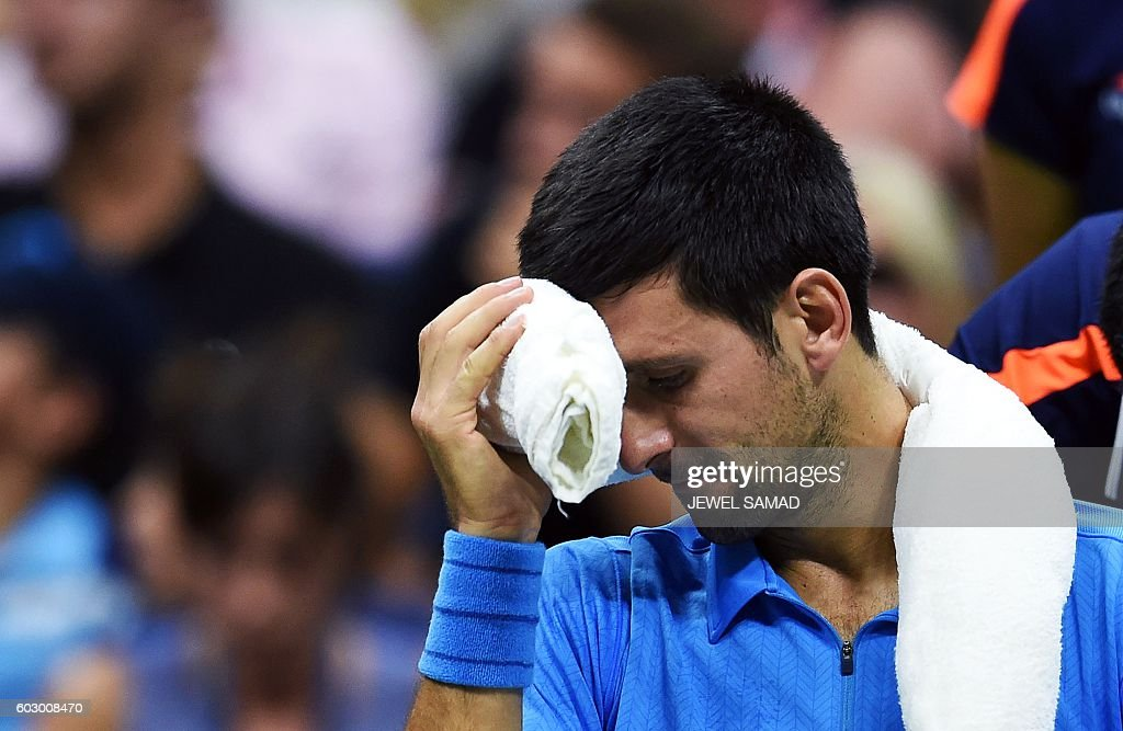TOPSHOT - Novak Djokovic of Serbia cools off during a break while playing against Stan Wawrinka of Switzerland in their 2016 US Open Men's Singles final match at the USTA Billie Jean King National Tennis Center in New York on September 11, 2016. / AFP / Jewel SAMAD