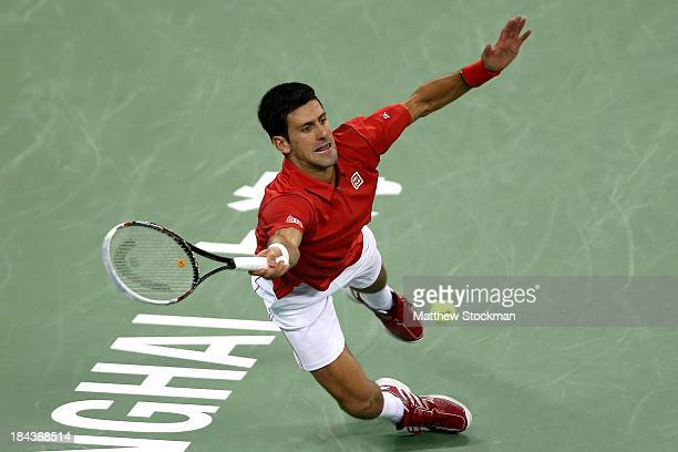 Novak Djokovic of Serbia dives for a shot while playing Juan Martin Del Potro of Argentina during the final of the Shanghai Rolex Masters at the Qi...