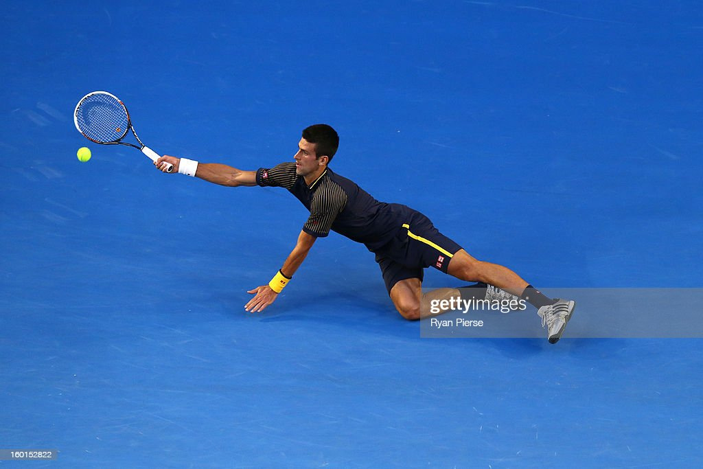 Novak Djokovic of Serbia dives to play a forehand in his men's final match against Andy Murray of Great Britain during day fourteen of the 2013 Australian Open at Melbourne Park on January 27, 2013 in Melbourne, Australia.