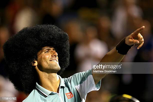Novak Djokovic of Serbia dons a wig and dances for the crowd after defeating Denis Istomin of Uzebekistan during the Rogers Cup at Uniprix Stadium on...