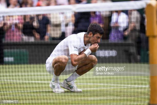 Novak Djokovic of Serbia eats a piece of grass after victory during the Men's Singles Final against Matteo Berrettini of Italy at The Wimbledon Lawn...