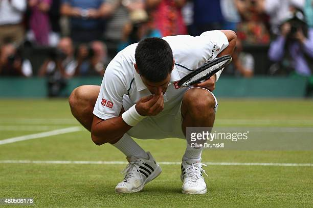 Novak Djokovic of Serbia eats the centre court grass after winning the Final Of The Gentlemen's Singles against Roger Federer of Switzerland on day...