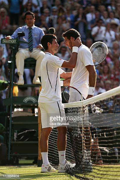 Novak Djokovic of Serbia embraces Juan Martin Del Potro of Argentina at the net after their Gentlemen's Singles semifinal match on day eleven of the...